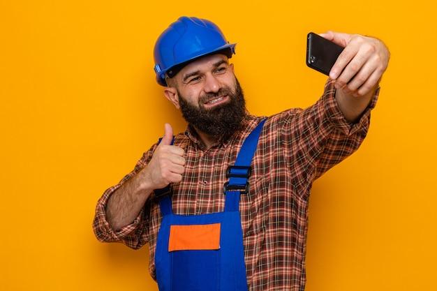 Brodaty budowniczy mężczyzna w mundurze budowlanym i kasku robi selfie za pomocą smartfona, uśmiechając się radośnie pokazując kciuk w górę