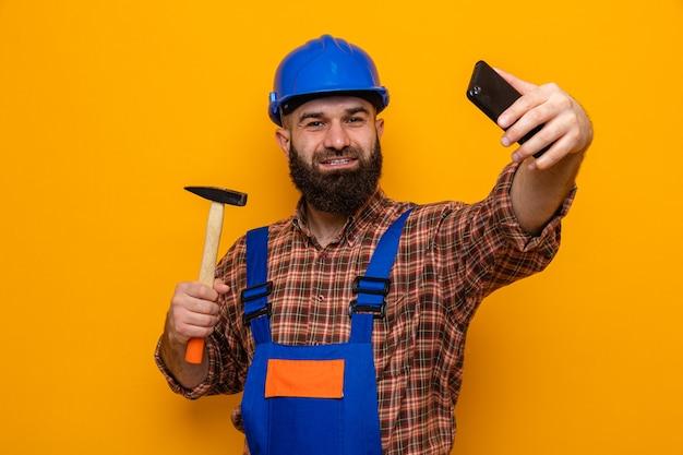 Brodaty budowniczy mężczyzna w mundurze budowlanym i kasku, trzymający młotek, robi selfie za pomocą smartfona, uśmiechając się radośnie