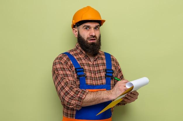 Brodaty budowniczy mężczyzna w mundurze budowlanym i kasku trzymającym schowek robiący notatki patrząc na kamerę zaskoczony stojąc na zielonym tle