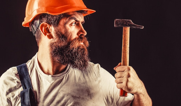Brodaty budowniczy na białym na czarnym tle. brodaty mężczyzna pracownik z brodą, kask budowlany, kask. uderzenie młotkiem. konstruktor w kasku, młotek, złota rączka, budowniczowie w kasku.