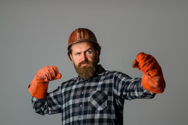 Brodaty budowniczy robotnik z rękawicami roboczymi budowniczy technologii budowlanej w kasku reklamowym