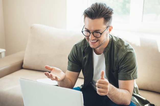 Brodaty chłopiec kaukaski w okularach o spotkanie online na laptopie w domu, siedząc na kanapie