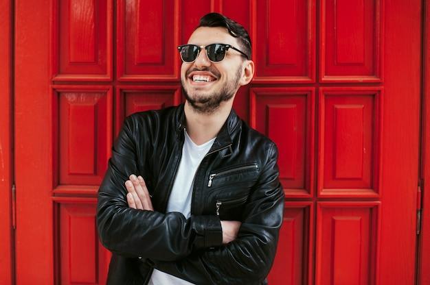 Brodaty chłopiec z pięknym uśmiechem pozowanie na tle czerwonych drzwi