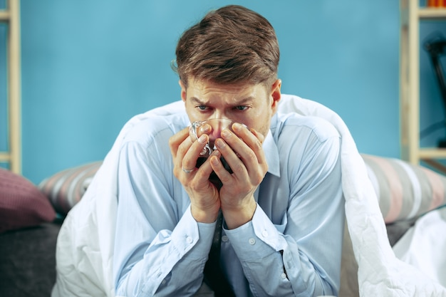 Brodaty chory mężczyzna z kominem siedzi na kanapie w domu i pije herbatę.