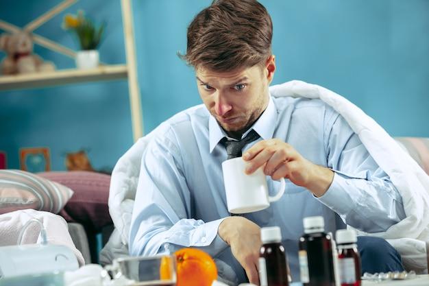 Brodaty chory mężczyzna z kominem siedzi na kanapie w domu przykryty ciepłym kocem i pije syrop z kaszlu.