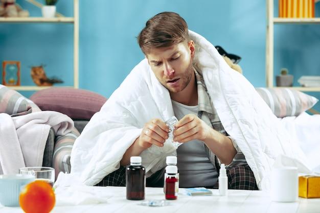 Brodaty chory mężczyzna z kominem siedzi na kanapie w domu przykryty ciepłym kocem z pigułkami. pojęcie choroby, grypy, bólu. relaks w domu. koncepcje opieki zdrowotnej.