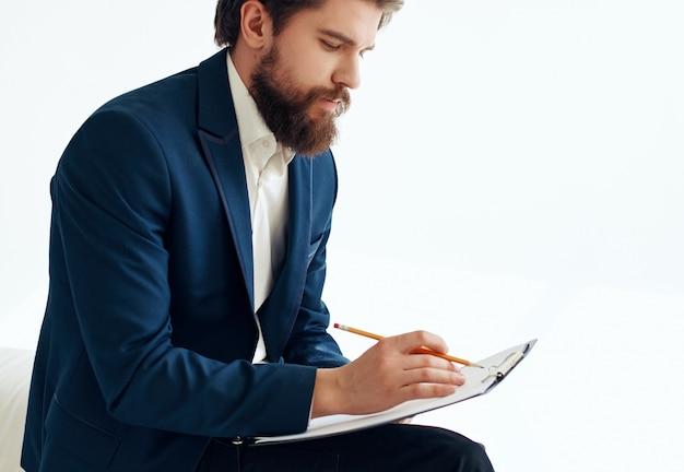 Brodaty człowiek biznesu w garniturze wznawia papierkową robotę