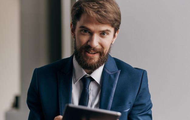 Brodaty człowiek biznesu z tabletem w ręku komunikowania pewności siebie. zdjęcie wysokiej jakości