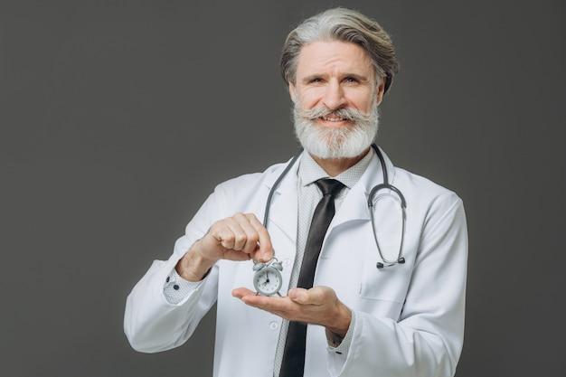 Brodaty czujnik lekarz trzymając budzik
