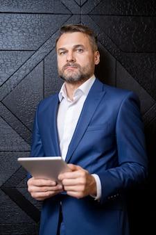 Brodaty dobrze ubrany biznesmen w średnim wieku z cyfrowym tabletem stojącym przy czarnej drewnianej ścianie