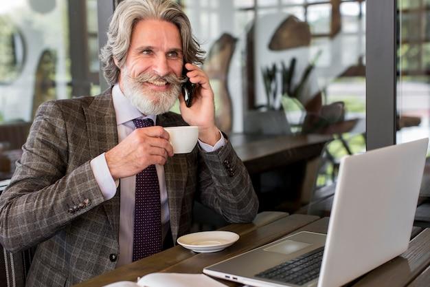 Brodaty dojrzały mężczyzna pije kawę w biurze