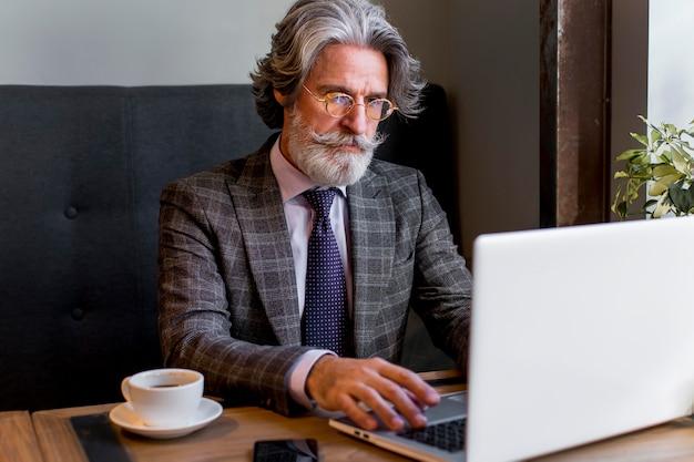 Brodaty dojrzały mężczyzna pracuje na laptopie
