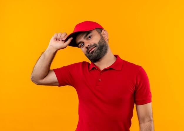 Brodaty doręczyciel w czerwonym mundurze i czapce z uśmiechem na twarzy dotykając czapki stojącej nad pomarańczową ścianą