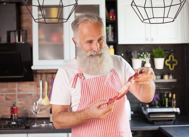 Brodaty dorośleć mężczyzna trzyma surowego wołowiny mięso.