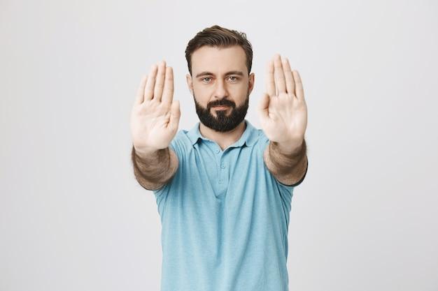 Brodaty dorosły mężczyzna wyciąga ręce do przodu, aby pokazać znak stopu