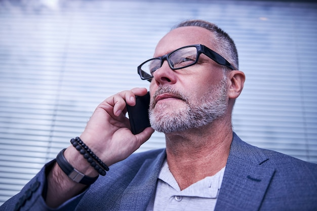Brodaty dżentelmen w okularach odwracający wzrok z poważnym wyrazem twarzy podczas rozmowy telefonicznej na świeżym powietrzu