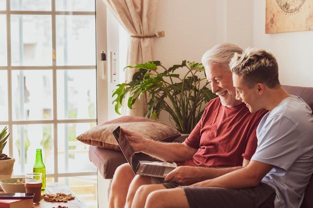 Brodaty dziadek i nastoletni wnuk siedzą razem na kanapie w domu i z rozbawieniem patrzą na ten sam laptop – dzielą te same zainteresowania lub pasje. pojęcie miłości rodzinnej