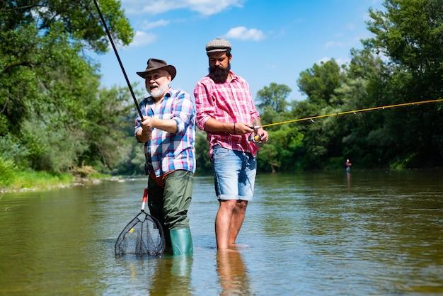 Brodaty, elegancki mężczyzna rybak sprzęt wędkarski wędkarstwo to zabawny człowiek relaksujący się i łowiący ryby przy doniczce nad jeziorem...