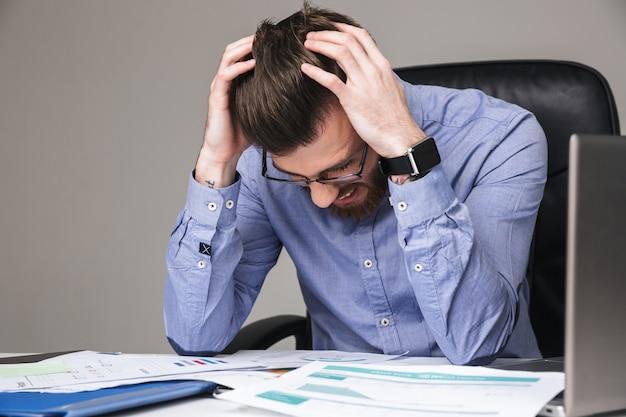 Brodaty elegancki mężczyzna w okularach w stresie trzymający głowę siedząc przy stole w biurze