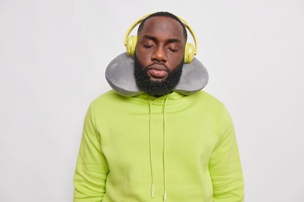 Brodaty etniczny mężczyzna drzemie podczas podróży w transporcie używa poduszki na szyję słucha muzyki ma zamknięte oczy nosi zieloną bluzę z kapturem pozuje w pomieszczeniach