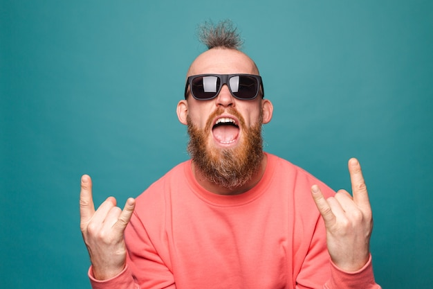 Brodaty europejczyk w swobodnej brzoskwini na białym tle, krzycząc z szalonym wyrazem, robi symbol rocka z rękami w górze
