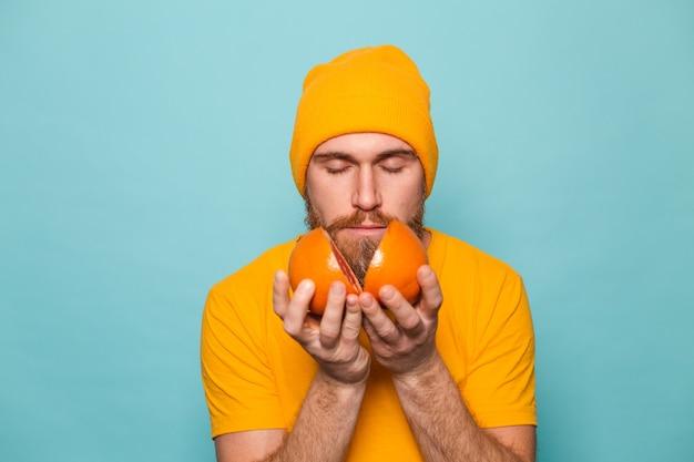 Brodaty europejczyk w żółtej koszuli na białym tle, pachnący pysznym grejpfrutem z zamkniętymi oczami