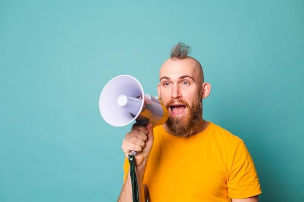 Brodaty europejczyk w żółtej koszuli na białym tle, szalony krzyk w megafon, uwaga!