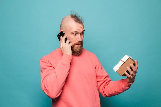 Brodaty europejski mężczyzna w dorywczo brzoskwinia na białym tle, trzymając prezent pudełko rozmowa na telefon komórkowy ze zdumioną, zszokowaną twarzą