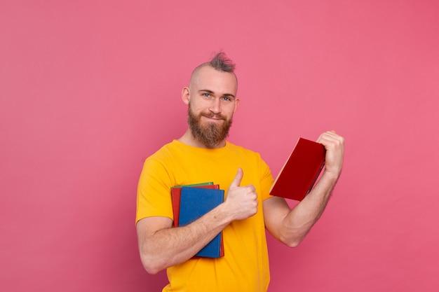 Brodaty europejski mężczyzna ze stosem książek na różowo