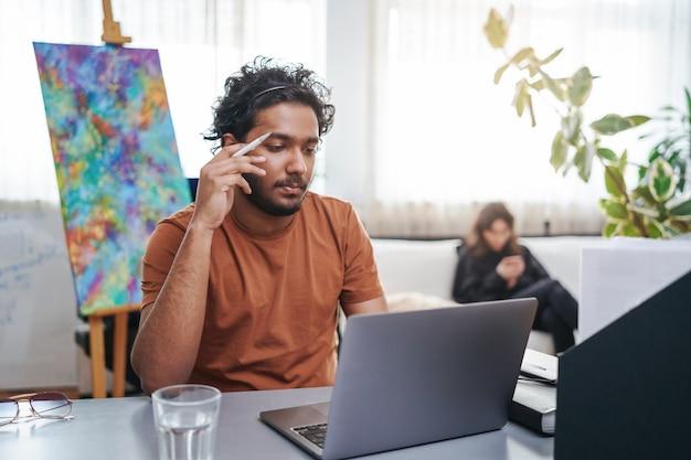 Brodaty facet indian wykonuje swoją pracę biurową na swoim laptopie, siedząc przy stole w nowoczesnym pokoju. zawód i praca biurowa.