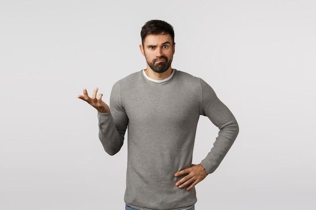 Brodaty facet nieświadomy w szarym swetrze