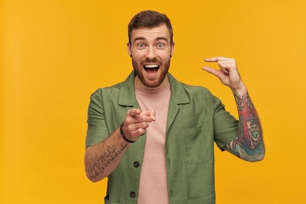 Brodaty facet, roześmiany mężczyzna z brunetką. ubrana w zieloną kurtkę z krótkim rękawem. ma tatuaż. pokazuje mały rozmiar i wskazuje na ciebie palcem. pojedynczo na żółtej ścianie