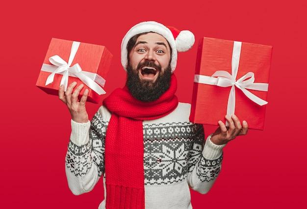 Brodaty facet santa hat krzyczy i demonstruje zapakowane prezenty
