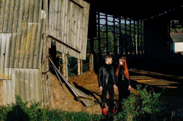 Brodaty facet stoi z dziewczyną w czarnych skórzanych kurtkach w stodole