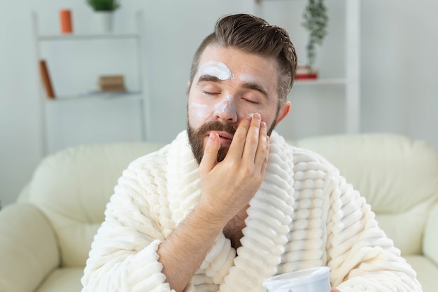 Brodaty facet stosujący krem do twarzy przed lustrzaną pielęgnacją skóry i spa dla koncepcji mężczyzny