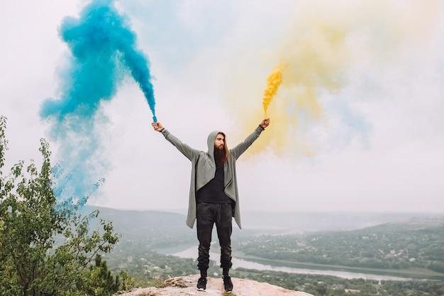 Brodaty facet trzyma kolorowy dym żółty i niebieski.