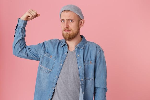 Brodaty facet ubrany w dżinsową koszulę wygląda na smutnego, nie może pochwalić się swoją siłą, niezadowolony ze swojej fizycznej formy, podniósł zgięte ramię, aby zademonstrować słabe mięśnie, z rozczarowaniem