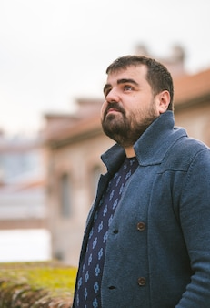 Brodaty facet w granatowym swetrze oparty o kamienną ścianę na ulicy, patrząc poważnie w niebo