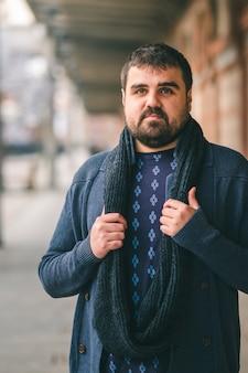 Brodaty facet w niebieskim swetrze stoi na ulicy z rękami na szaliku