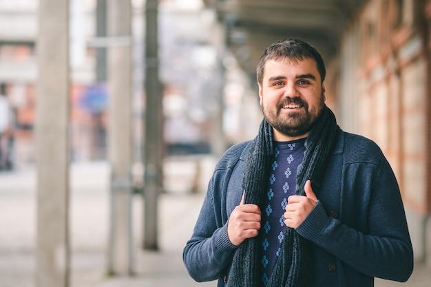 Brodaty facet w niebieskim swetrze stojący na ulicy z rękami na szaliku patrząc w kamerę