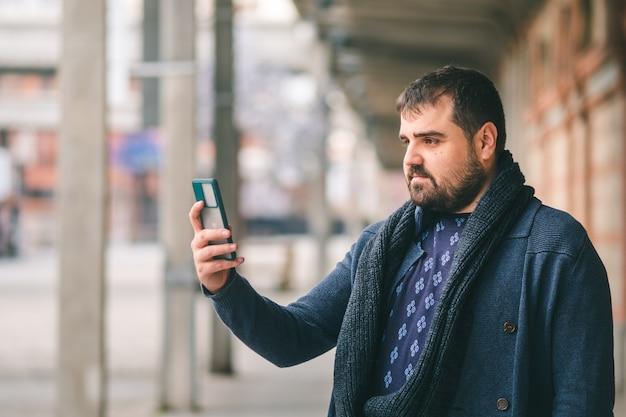 Brodaty facet w niebieskim swetrze stojący na ulicy za pomocą swojego smartfona