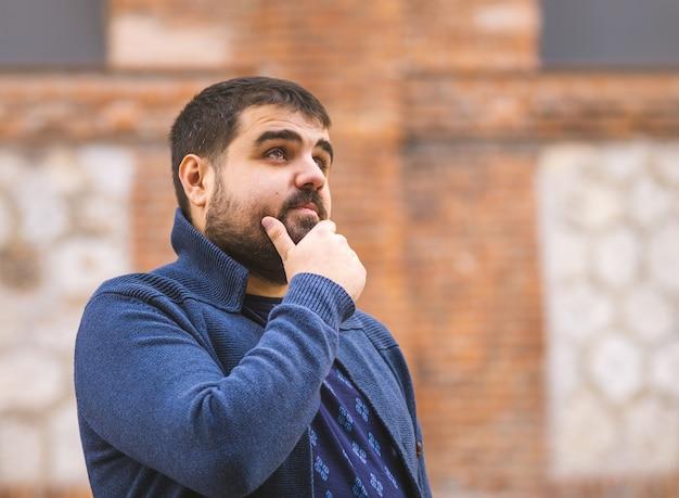 Brodaty facet w niebieskim swetrze zamyślony patrząc na ulicę