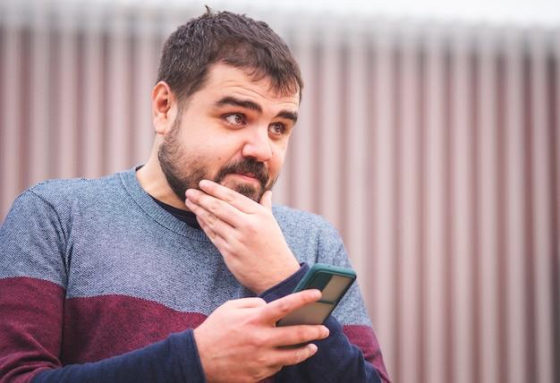 Brodaty facet w swetrze, używając swojego smartfona na ulicy