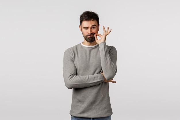 Brodaty facet w szarym swetrze utrzymujący w tajemnicy