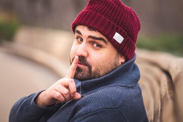 Brodaty facet w wełnianym kapeluszu i swetrze siedzi na ławce w parku patrząc w kamerę i prosząc o ciszę