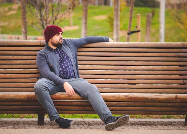 Brodaty facet w wełnianym kapeluszu i swetrze siedzi na ławce w parku relaksując się