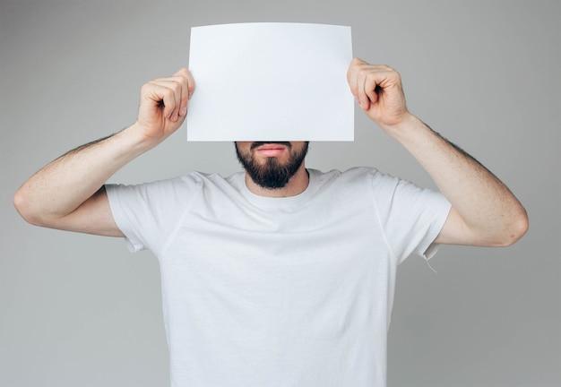 Brodaty facet zakrywa część twarzy z białą pustą stroną. trzymaj go obiema rękami
