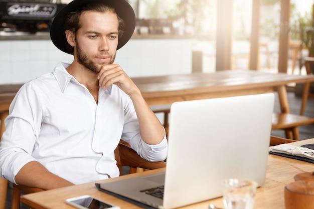 Brodaty freelancer łączący się z siecią bezprzewodową przez laptopa. przemyślany mężczyzna pracuje na notebooku, siedząc przy drewnianym stole w nowoczesnym wnętrzu kawiarni. student czytanie książki w kawiarni