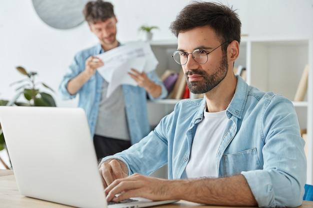 Brodaty freelancer pracuje na laptopie, klawiaturach informacji, myśli o zyskach