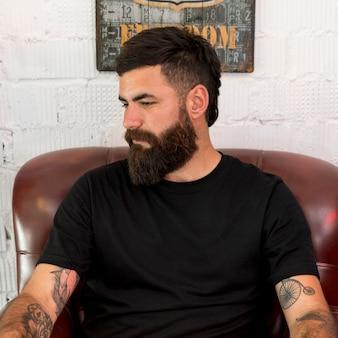 Brodaty fryzjer siedzi na krześle w salonie fryzjerskim